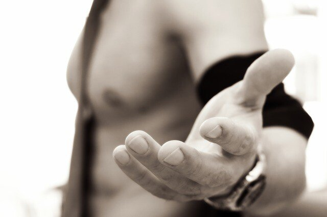 man without a shirt on reaching out his hand